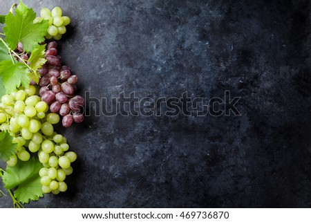 Red and white grapes over stone table. Top view with copy space