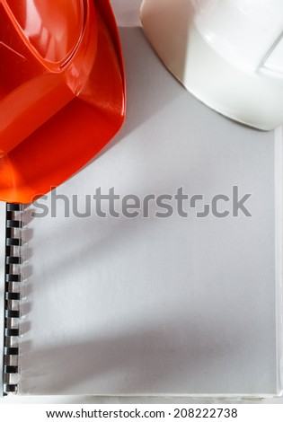 Red and white helmets on blank notebook - stock photo