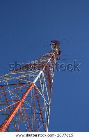 Red and white high voltage power tower in the blue sky.