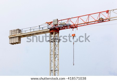 Red and white  hoisting crane on blue sky. - stock photo
