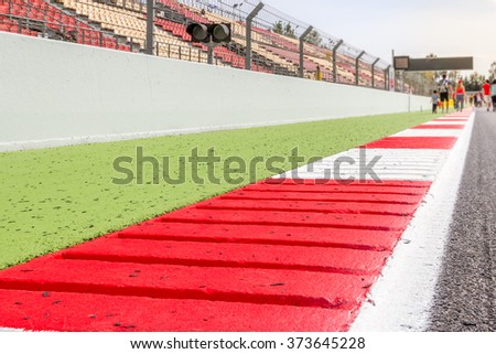 Red and white kerbs of a race track with people on the background - stock photo