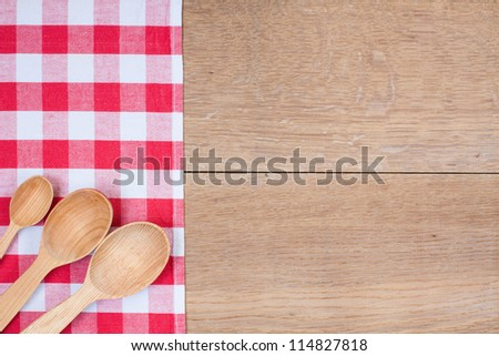 Red and white kitchen textile texture, wooden spoons on wood textured background - stock photo