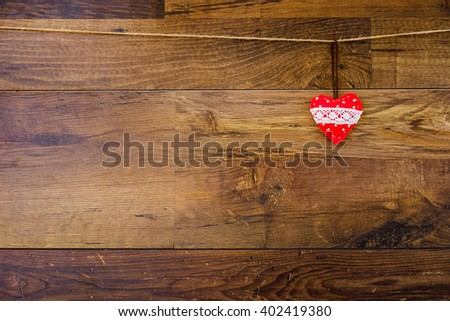 Red and white lace heart hanging on the clothesline on wooden background. Vintage style. Concept image for Valentines day season. Love postcard on wood texture with copy space for text.  - stock photo
