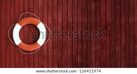 Red and white life buoy hanging on the side of a wooden ship - stock photo