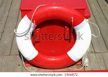 Red and white Life Buoy on a boat. - stock photo