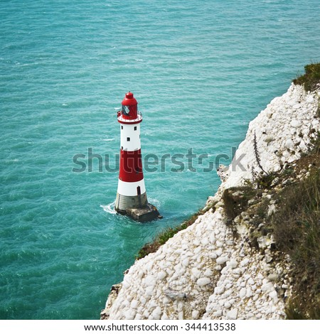 Red and white lighthouse closeup in cyan sea with cliffs - stock photo