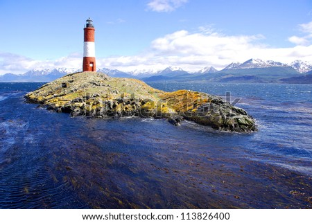 Red and white lighthouse in blue sky in the Beagle Channel Ushuaia Patagonia Argentina - stock photo