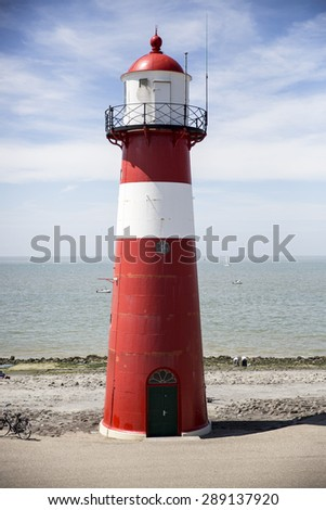 Red and white lighthouse on a blue sky background, Westkapelle, The Netherlands - stock photo
