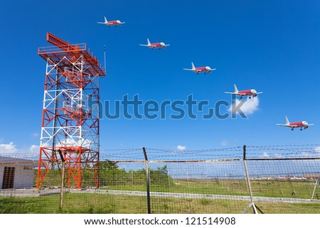 Red and white metal radar tower in airport area with multiple exposure landing plane - stock photo