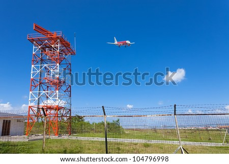 Red and white metal radar tower in airport area with plane landing - stock photo