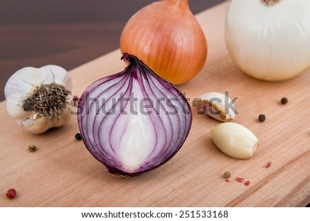 Red and white onion, garlic and spices on a wooden board - stock photo