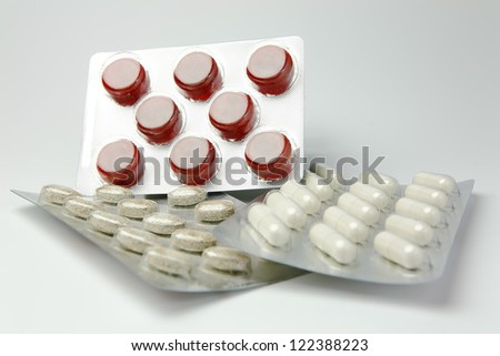 Red and white pills on a table with white background