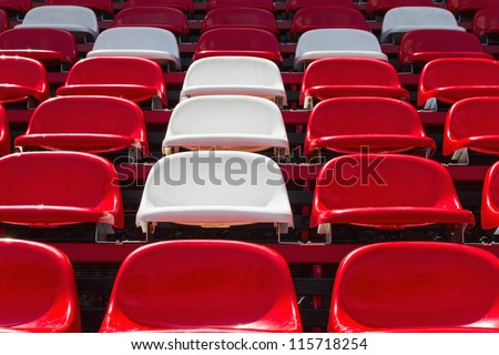 Red and white plastic seats in stadium - stock photo
