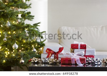 red and white presents by christmas tree in modern living room - stock photo