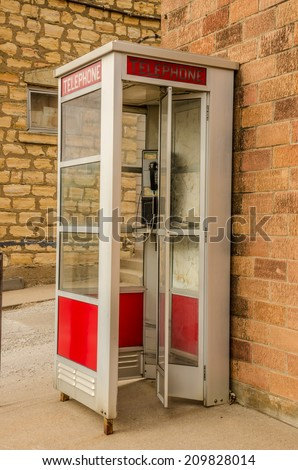 Red and white public telephone booth with a push button phone. - stock photo
