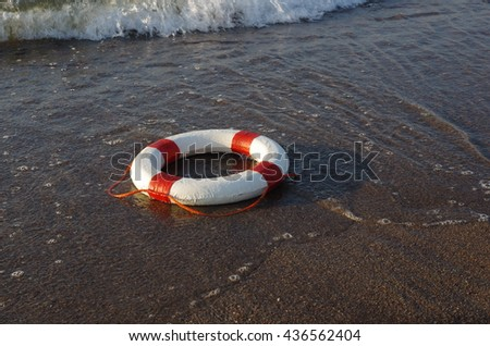 red and white rescue wheel on a sea background - stock photo
