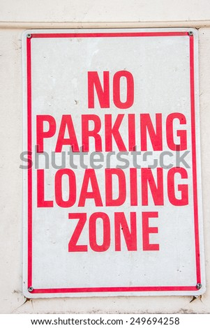 Red and white sign for no parking in the loading zone