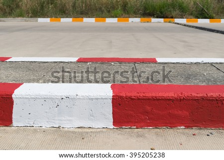 Red and White sign on road with yellow and white sign background