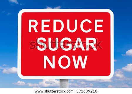 Red and white signpost REDUCE SUGAR NOW  in front of a blue sky, symbol for the health risk or danger of high sugar intake, spoof of british roadsigns - stock photo