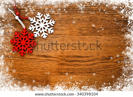 Red and white snowflake on a wooden snowy background - stock photo