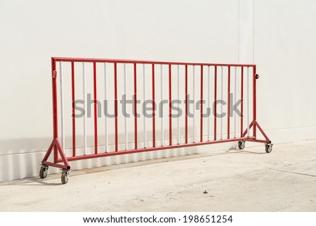 Red and white steel barrier on wheel on the wall