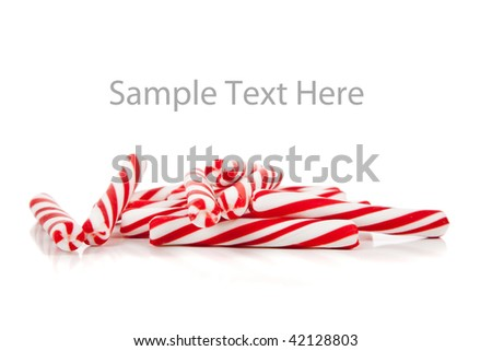 Red and white striped candy canes on a white copy space - stock photo