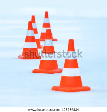 Red and white striped cones on the ice - stock photo