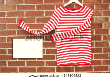 Red and white striped shirt inviting with sign copyspace