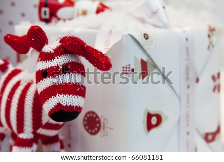 Red and white striped toy reindeer and a wrapped gift box. - stock photo