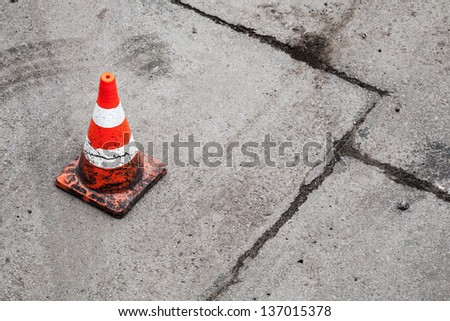 Red and white striped warning cone on dirty asphalt road - stock photo