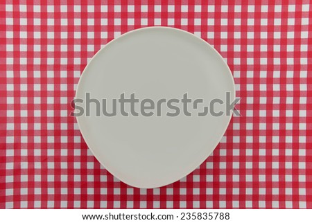 Red and White table cloth with white plate - stock photo