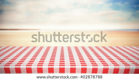 Red and white tablecloth against serene beach landscape - stock photo