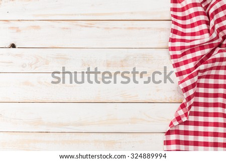 Red and white tablecloth on white wooden table - stock photo