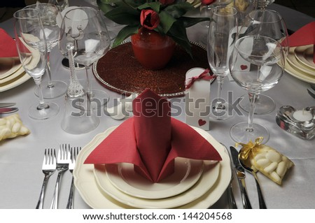 Red and white theme wedding breakfast dining table setting with red table napkins in bishop style folds, for weddings or Valentine day banquet meal.