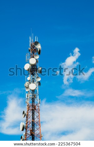 Red and white tower of communications with a lot of different antennas under blue sky and clouds