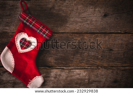 Red and white traditional Christmas sock on wooden background with blank space - stock photo