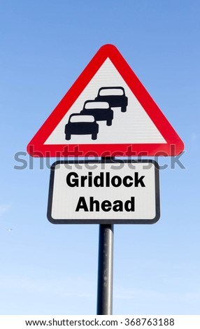 Red and white triangular road sign with a Gridlock Ahead concept against a partly cloudy sky background