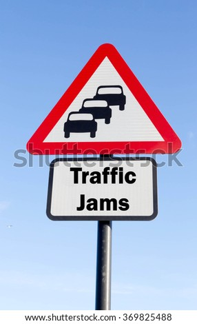 Red and white triangular road sign with a Traffic Jams Ahead concept against a partly cloudy sky background