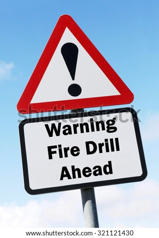 Red and white triangular road sign with a Warning of a Fire Drill ahead concept against a partly cloudy sky background - stock photo