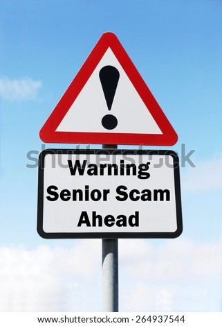 Red and white triangular road sign with a warning of a Senior Scam Ahead concept against a partly cloudy sky background - stock photo