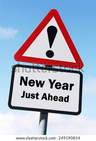 Red and white triangular  road sign with a warning of The New Year Just Ahead concept against a partly cloudy sky background - stock photo