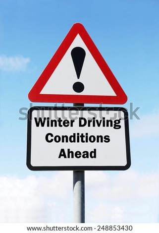 Red and white triangular  road sign with a warning of Winter Driving Conditions Ahead concept against a partly cloudy sky background - stock photo