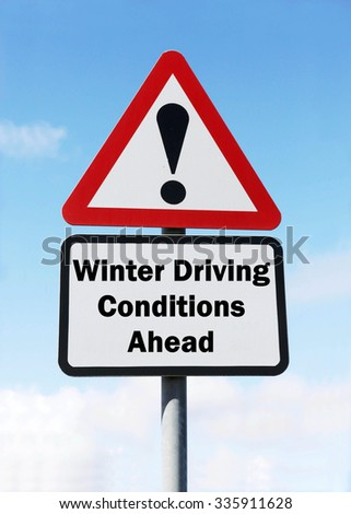 Red and white triangular road sign with a Winter Driving Conditions Ahead concept against a partly cloudy sky background - stock photo