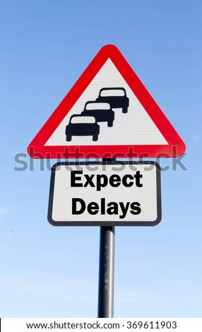 Red and white triangular road sign with an Expect Delays Ahead concept against a partly cloudy sky background