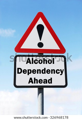 Red and white triangular road sign with warning of Alcohol Dependency Ahead concept against a partly cloudy sky background - stock photo