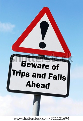 Red and white triangular road sign with warning to Beware of Trips and Falls ahead concept against a partly cloudy sky background  - stock photo