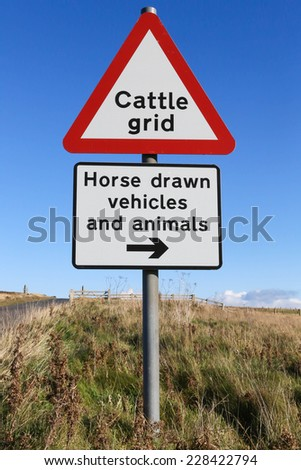 Red and white triangular warning road sign indicating a 'Cattle Grid' ahead