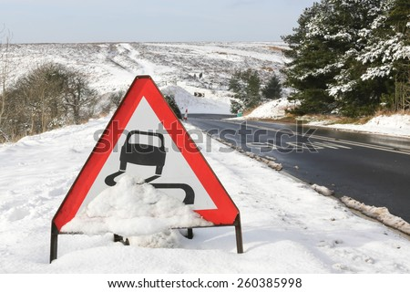 Red and white triangular warning road sign indicating slippery road conditions in wintry conditions. - stock photo