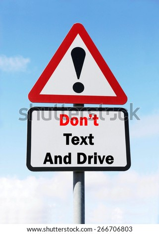 Red and White triangular warning road sign with a Don't Text And Drive concept against a partly cloudy sky background.