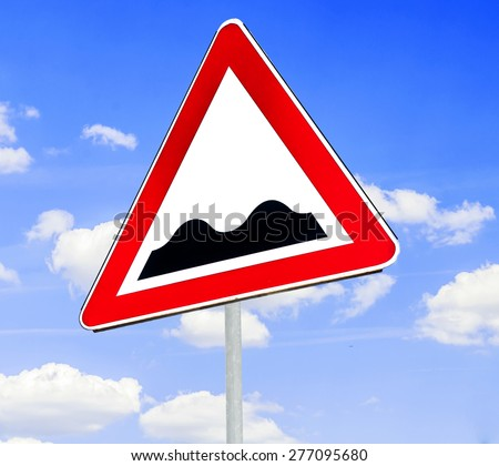 Red and white triangular warning road sign with a warning of a bumpy road ahead concept against a clear blue sky background - stock photo